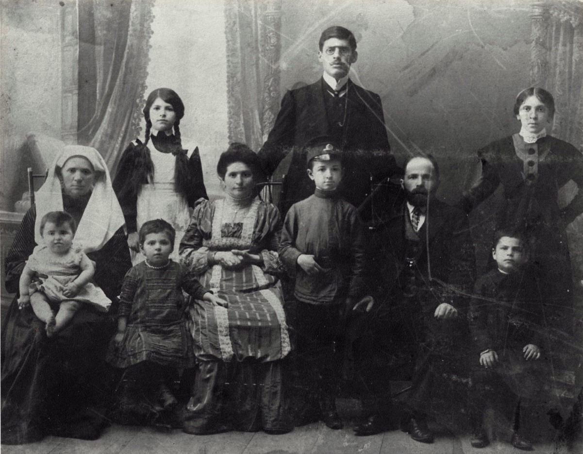 The woman on the far left with the white head covering is Gitel Schumuter Goldman. Her husband was Yallik Goldman, and the people she is posed with are members of the Goldman family.