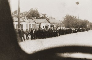 Jewish deportees under German guard march through the streets of Kamenets-Podolsk to an execution site outside of the city. Photo by Gyula Spitz
