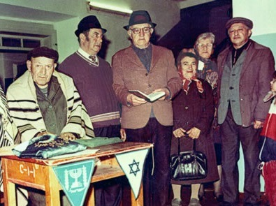 """Rededication ceremony celebrating the return of one room of the synagogue to the Jewish community, 1991. Photograph by <a href=""""http://www.jewishgen.org/"""">Miriam Wainer</a>."""
