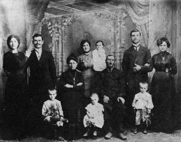 Family group picture taken in Justingrad 1912 on the eve of the departure for America of newlyweds David Feldstein (1884 – 1964) and Adella Logvin Feldstein (1892-1973) Standing left. Seated center, Adella's parents, David Logvin (d. 1916?) and Blume Leah Logvin (d. 1937, Brooklyn): she was blinded in a 1919 pogrom. Behind them, infant Leo Troy (d. 1981, Scranton), in the arms of his mother, Adella's sister Maryam Troyaker (later Firdman) who was killed in the Nazi Holocaust with her other children. Standing right, Adella's brother Lazar Logvin (d. 1969, Buffalo) with his wife Esther Krenzel Logvin (d. 1918).