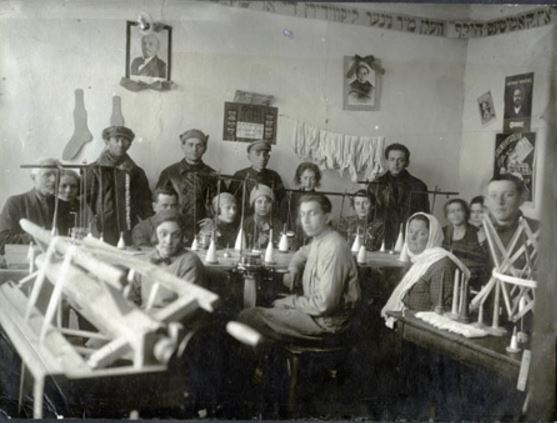Portrait of workers at knitting machines in a hosiery factory of the town's Relief Society