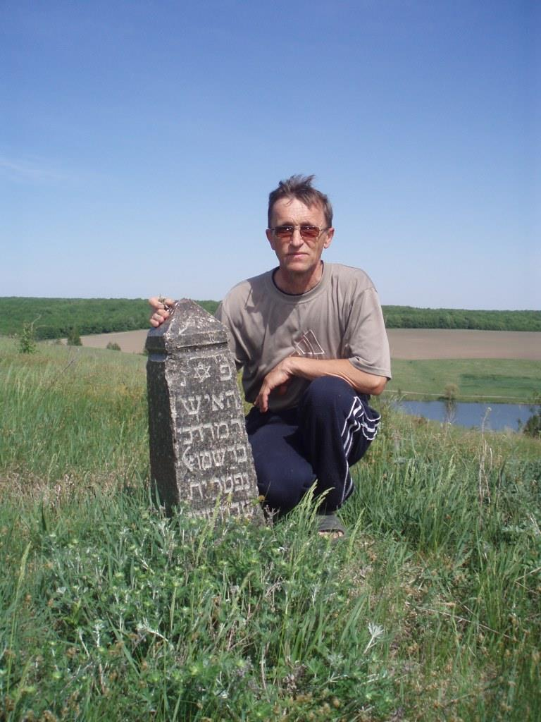 Local historian Leonid Lashchenko with Jewish gravestone in the field near Tarashcha, 2016