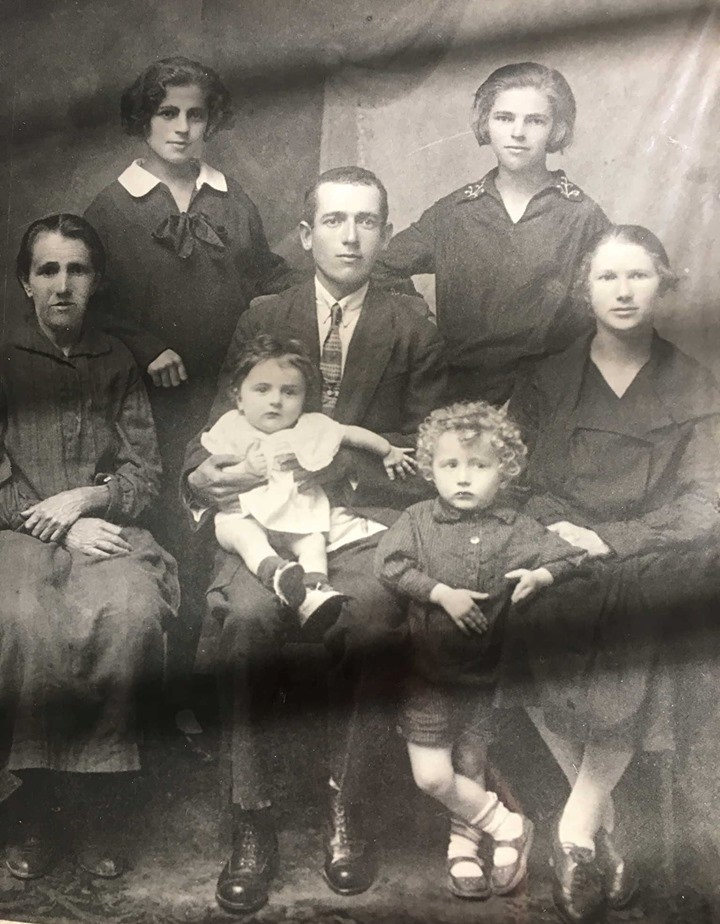 Sherman family in Veledniki, 1935. Photo was shot in Shmerman's house and provided by Sophia Sherman in 2021. Baby being held by Benjamin Sherman = Lossel, blonde hair kid - Michael(lived in Israel, died in 2020), right of Benjamin wife, left Benjamin - Khashia (Samuel Sherman's Wife). Benjamin was killed by Nazis.