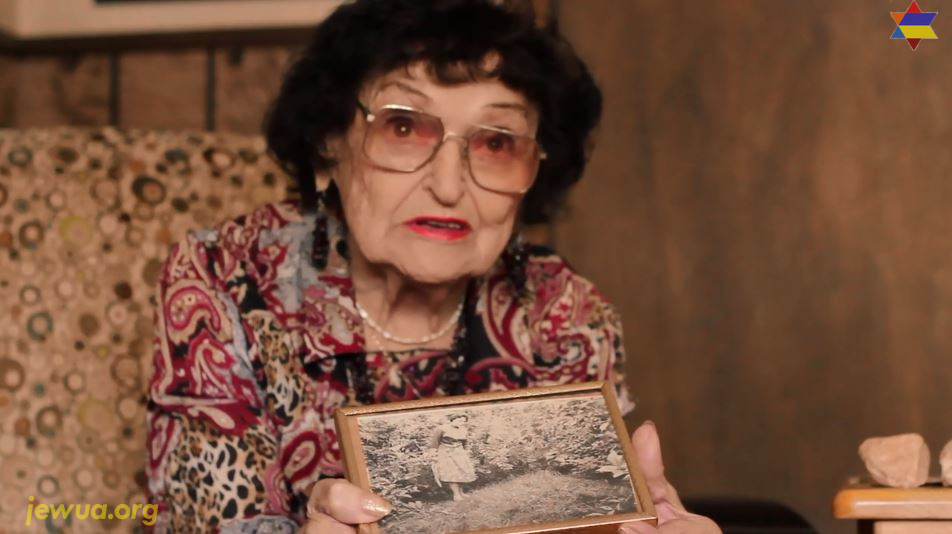Holocaust survivor Klara Vinocur with post-WWII photo of Shpola Holocaust mass grave