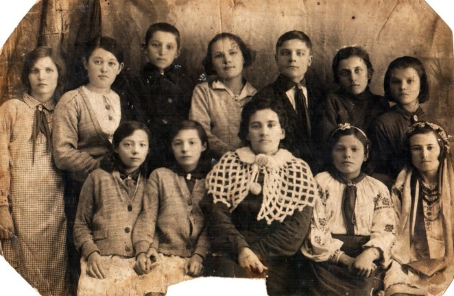 Students of the 6th grade of Alexandrovka school with their teacher. January 1, 1940. Katerina Boguslavska (Gorbanyova) - the second on the left in the second row; Kila Kleiman - in the wreath. The teacher (in the center) was shot by the fascists during the Nazi occupation.